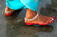 Indian woman´s feet decorated with anklet and red color.