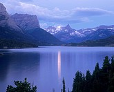 Full moon sets at dawn over Fusillade Mountain and St  Mary Lake, Glacier National Park, Montana, USA