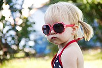 A one year old toddler wearing bright red sunglasses on Independence Day in Liberty Lake, Washington, USA.
