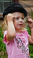 This vertical image shows a cute 2 year old Caucasian girl, wearing a black vintage hat with a veil over her face