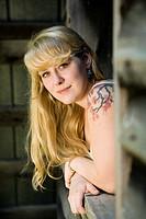 Portrait of young woman looking through barn window - Cedar Mountain, North Carolina, USA
