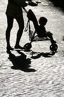 mother pushing pram buggy in street