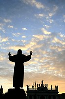 Saint francis of Assisi statue and san giovanni basilica church at sunset in rome