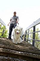 A man, 30-35 years, with his Samoyed dog in Spokane, Washington, USA.