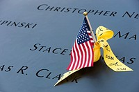 A small American flag and a yellow ribbon left on the names inscribed in the perimeter of one of the pools at the National September 11 Memorial in Ne...