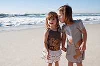 Two baby girls holding hands at the beach