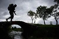 Silhouette of hiker crossing bridge along the Camino de Santiago, route Frances