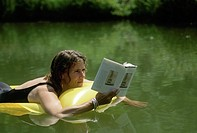 Woman, 30-40 years old, reading book while floating in water on an inflatable raft. Midwest, USA