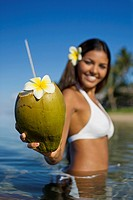 Smiling, attractive local girl holds out a coconut with straw and flower ready to drink at Lahaina, Maui, Hawaii