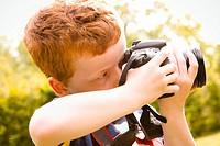 A Young boy, aged 7, using a digital SLR camera in a sunny garden