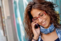 Cute curly young woman talking on her mobile phone