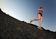 Woman jogger over lava field, Big Island, Hawaii, USA