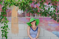 Woman sitting under painted tree with real leaves, Thousand Oaks, California, USA