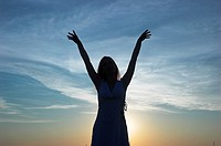 Silhouette of a young woman at dusk arms raised