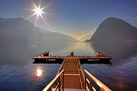 Jetty in the winter sun with seagulls in Lugano, Ticino, Switzerland, overlooking the mountain of Lugano, Monte San Salvatore