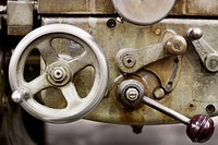 A metal wheel and lever on a piece of metalworking machinery.