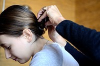 Mother´s hands fixing girl´s hair