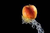 Splashing water on red apple