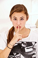 Young teenage girl putting her finger in front of her mouth