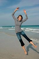 woman jumping next to seaside