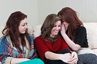 UK Great Britain Europe Three teenage girls sitting on a sofa, one twin whispering to their friend with the other twin left out of the conversation