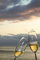 Two champagne flutes toasting against ocean background