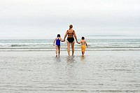 a grandmother walking into water at beach with two children in hands