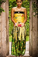 A Balinese woman holding a floral arrangement dress in a traditional Balinese dress