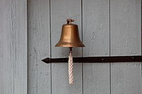 A small ship´s bell hanging on a white wooden door