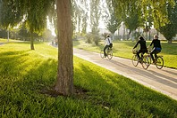 people cycling by the Turia park, Valencia, Spain