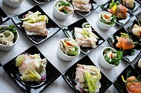 Fish entrée served on white plates and black dishes