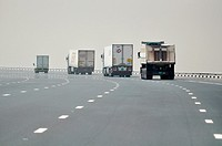 Abu Dhabi, United Arab Emirates: trucks along a road through the desert