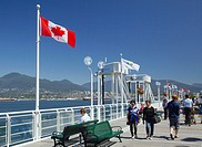 People walking on the deck beside Canada Place, with Canadian flags in the background