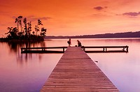Sunset over a lake with a small boat dock and fishermen silhouetted in the foreground, Lake Guntersville State Park, Alabama, USA.