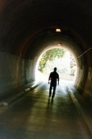 Mysterious blurred male figure walking in tunnel