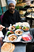 An Egyptian man enjoys a traditional breakfast- Fuul Fava beans with bread and salad in a small street restaurant in Cairo