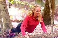 A 38 year old blond woman wearing work-out clothing doing a push-up on a log in a forest setting in the fall