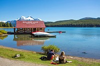 Couple sitting on bank of Maligne Lake with boathouse In Jasper National Park in Alberta Canada