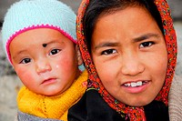portrait of child carrying younger sister at the back