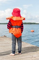 Young child wearing orange life jacket and red hat watching the sea from a wooden jetty