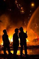 Firemen controlling fire during the cremà, fallas festival. Valencia. Spain. 2013