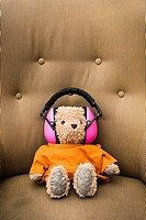 Conceptual image of teddybear wearing orange sweater and pink hearing protection sitting in armchair.