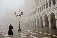 A man walks in St. Mark´s Square In Venice covered in thick fog, Italy.