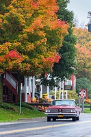 Vintage car driving through the picturesque town of Weston in the Indian Summer, Vermont, USA