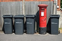 Maidstone, Kent, England. Row of household rubbish bins and red letterbox.