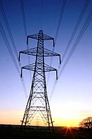 An electricity pylon of the National Grid in Wales at sunset.
