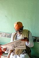 Senior man reading newspaper in cafe, Mandvi, Gujarat, India