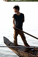 Portrait of a young fisherman at work on the Mekong River early in the morning outside of Phnom Penh, Cambodia.