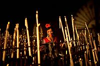 A woman lights a candle in the Votive Room of the shrine of the Virgin of Rocio, in Almonte, Donana National Park, Huelva province, Andalusia, Spain, ...