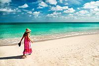 Girl walking along an empty beach in Turks & Caicos Islands.